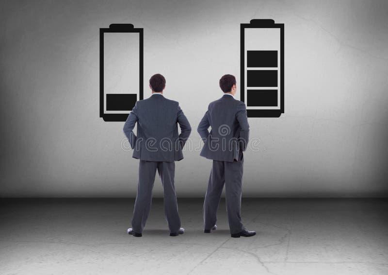 Baixa bateria e bateria carregada com o homem de negócios que olha em sentidos opostos imagem de stock royalty free