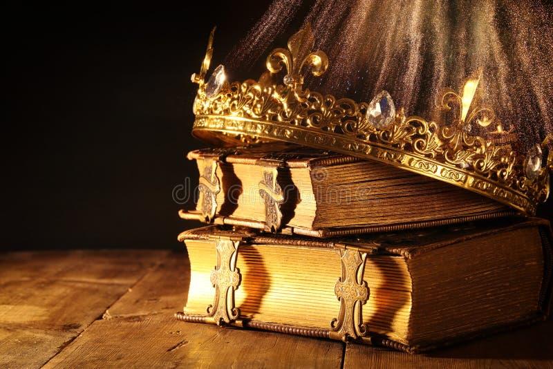 baixa chave da rainha/coroa bonitas do rei em livros velhos Vintage filtrado período medieval da fantasia fotografia de stock