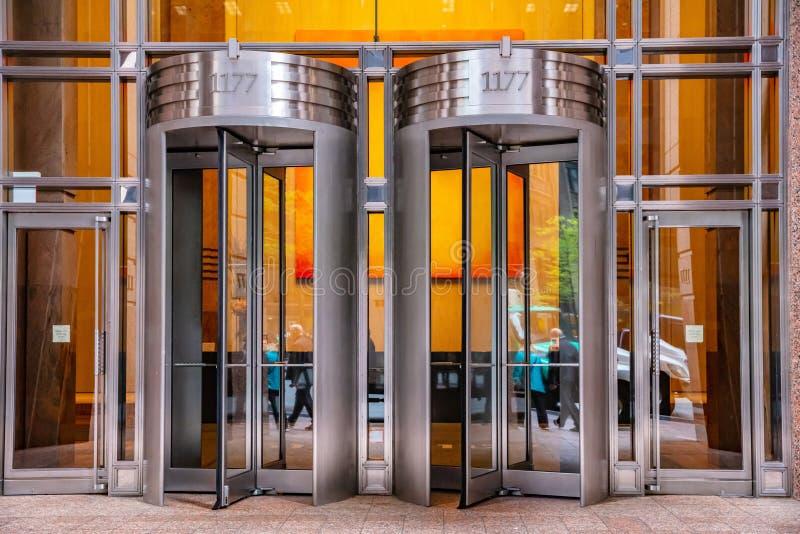 Baixa de New York, Manhattan Portas giratórias na fachada de construção de vidro fotos de stock