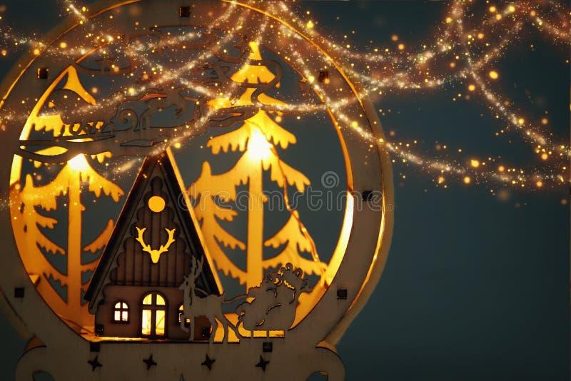 Baixa imagem chave da cena mágica do Natal da floresta, da cabana e de Papai Noel de madeira do pinho sobre o trenó com cervos fotos de stock