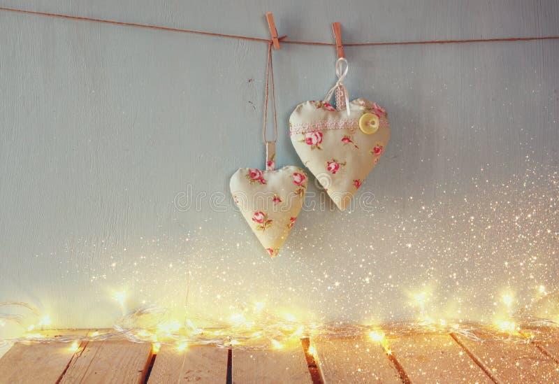 Baixa imagem chave da imagem do Natal dos corações da tela que penduram na corda na frente do fundo de madeira Retro filtrado imagem de stock