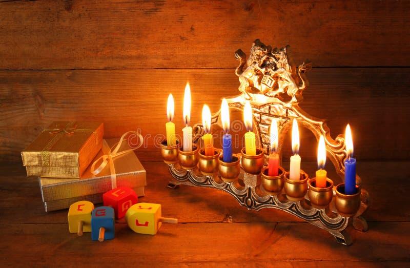 Baixa imagem chave do Hanukkah judaico do feriado com menorah (candelabros tradicionais), anéis de espuma e dreidels de madeira ( imagens de stock royalty free
