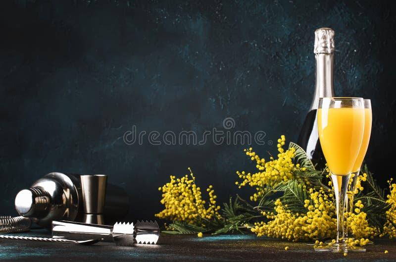 Baixa mimosa do cocktail do álcool com suco de laranja e champanhe ou vinho espumante seco frio nos vidros, fundo azul com flores imagem de stock