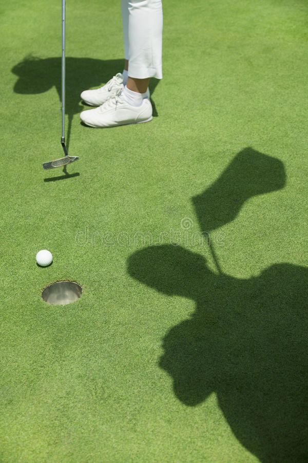 Baixa seção da jovem mulher que bate a bola no campo de golfe, foco no furo imagens de stock