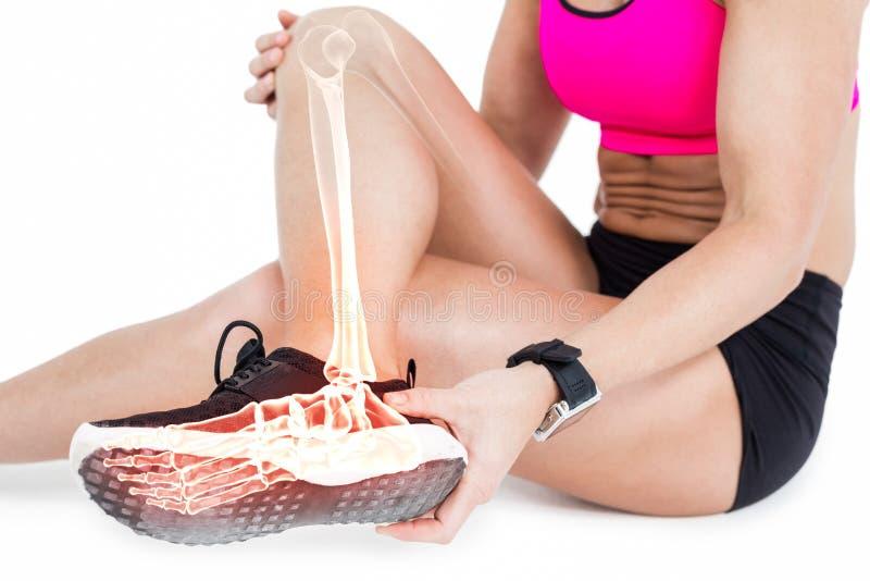 Baixa seção da mulher que sofre da dor do tornozelo no fundo branco foto de stock royalty free