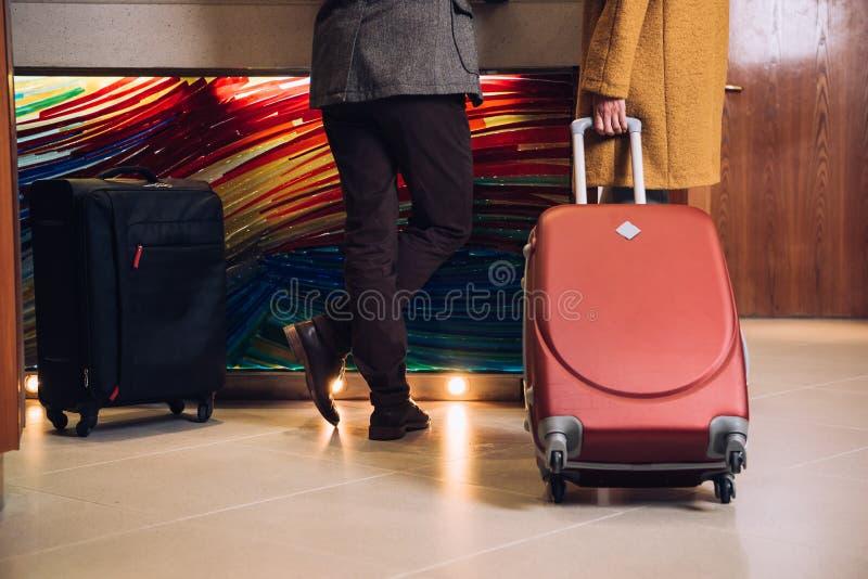 baixa seção de pares maduros com as malas de viagem que estão na recepção foto de stock royalty free