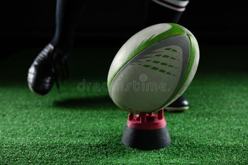 Baixa seção do atleta masculino que retrocede a bola de rugby no T foto de stock