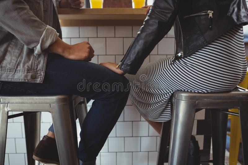 Baixa seção dos pares no tamborete no café imagem de stock royalty free