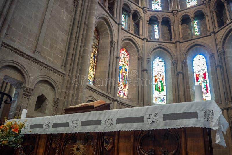 Baixo ângulo da Bíblia na tabela de madeira no muro de cimento com fundo bonito das janelas do mosaico na catedral de Lausana foto de stock