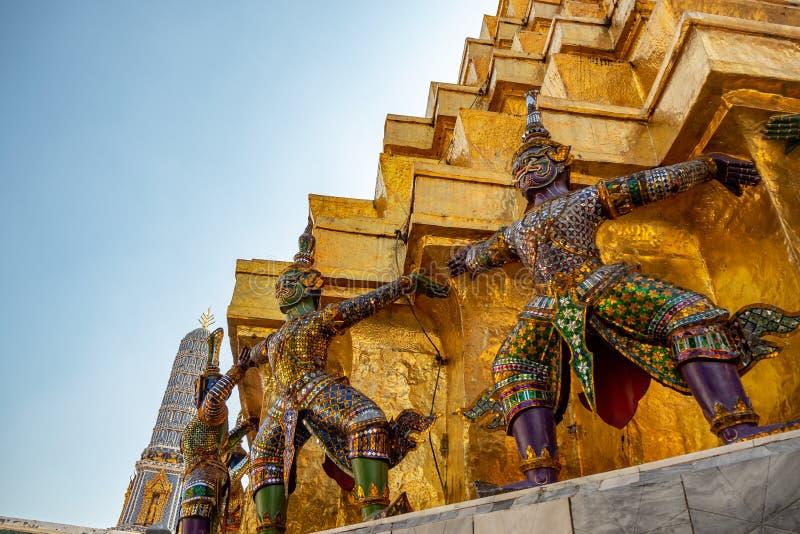 Baixo ângulo de estátuas gigantes na base do pagode dourado no templo real no palácio grande com fundo claro do céu azul foto de stock