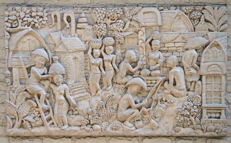 Baixo relevo que representa a vida da vila tailandesa antiga foto de stock royalty free