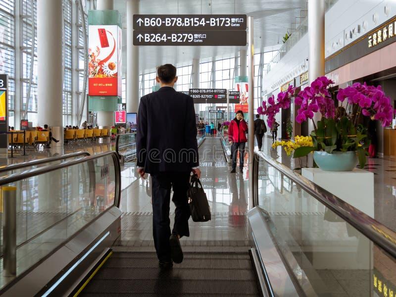 BAIYUN, GUANGZHOU, CHINA - 10 BRENG 2019 in de war – Achtermening van een reiziger die in pak naar zijn het inschepen poort in Ba stock fotografie