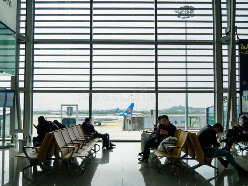 BAIYUN, GUANGZHOU, CHINA - 10 BRENG 2019 in de war - Passagiers zit en wacht bij een het inschepen poort binnen de Internationale stock fotografie