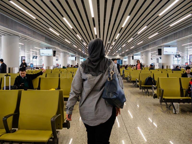 BAIYUN GUANGZHOU, KINA - 10 MARS 2019 - en muslimsk kvinna i hijab/sjalett går till hennes stiga ombord port på internationella B royaltyfria foton