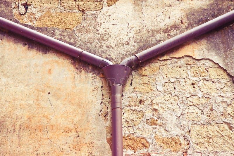 Bajada de aguas de cobre vieja contra un yeso y una pared de piedra - agua de lluvia fotografía de archivo libre de regalías