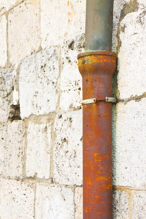 Bajada de aguas vieja contra una pared de piedra - Italia del arrabio y del cobre fotografía de archivo libre de regalías