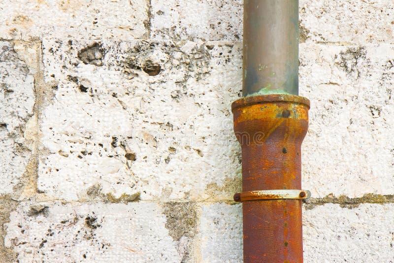 Bajada de aguas vieja del arrabio y del cobre contra una pared de piedra fotos de archivo libres de regalías