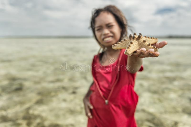 Bajau tribe girl picked up star fish from sea and trying to sell that to tourist, Sabah Semporna, Malaysia royalty free stock photos
