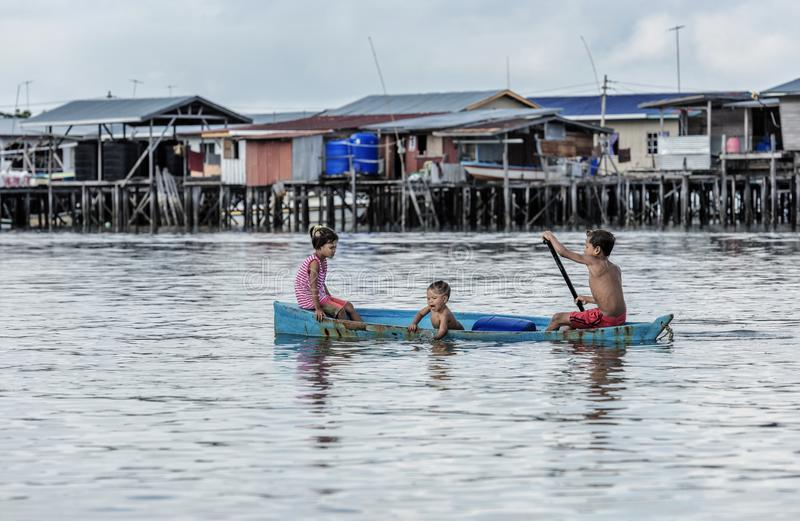 Bajau tribe kids having fun by rowing small boat near their village houses in Sea, Sabah Semporna, Malaysia royalty free stock image