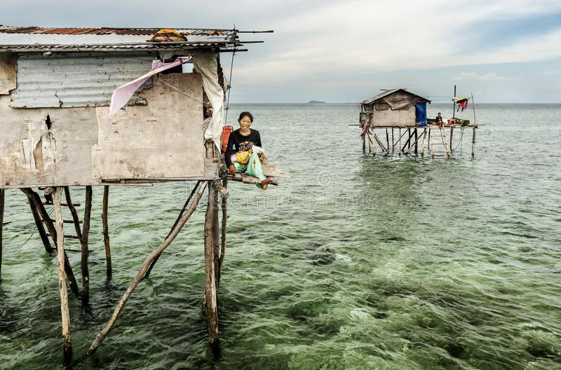 Bajau tribe mother sitting her wooden house in Sabah Semporna, Malaysia royalty free stock images