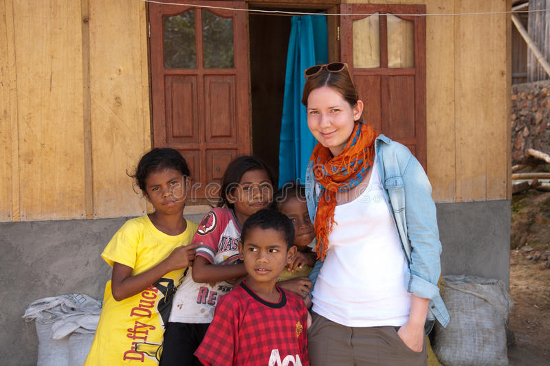 BAJAWA, FLORES - INDONESIA - CIRCA JULY 2013: Humanitarian worker. With children in local tribe stock image