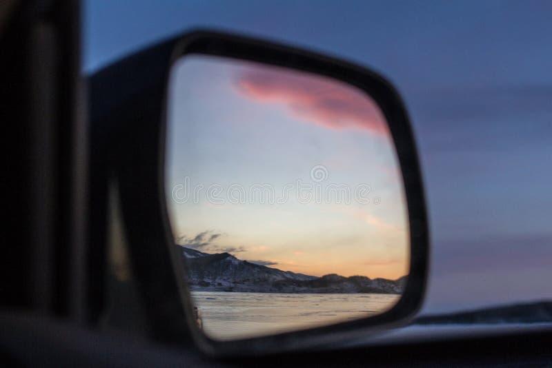 Bajecznie piękny różowy zmierzch odbijał w lustrze odległy widok samochód na Jeziornym Baikal w zimie zdjęcie royalty free