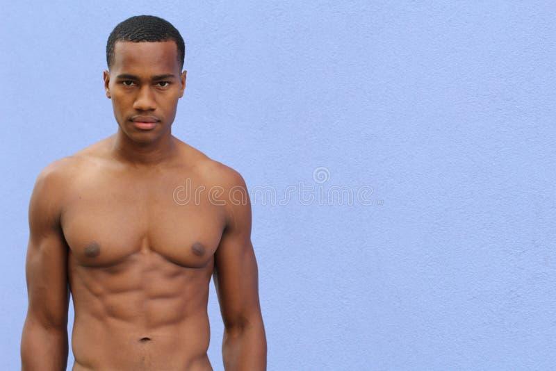 Bajo sol, un hombre negro masculino, medio desnudo, está haciendo una pausa un callejón con la expresión áspera foto de archivo libre de regalías