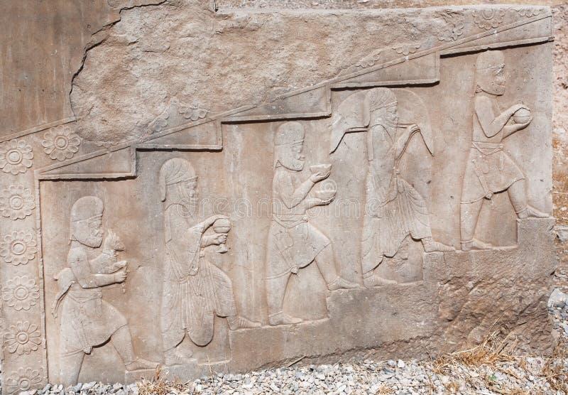 Bajorrelieve de piedra con imágenes de la gente que trae la comida y animales, como donaciones, en Persepolis histórico, Irán foto de archivo libre de regalías