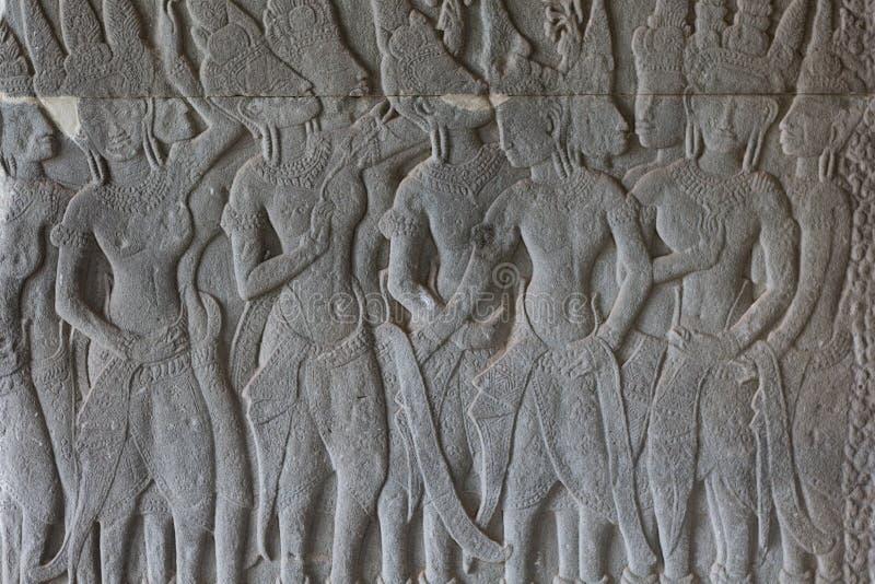 Bajorrelieve de piedra con las figuras humanas en el templo de Angkor Wat, Siem Reap, Camboya Figura masculina talla de piedra en fotos de archivo