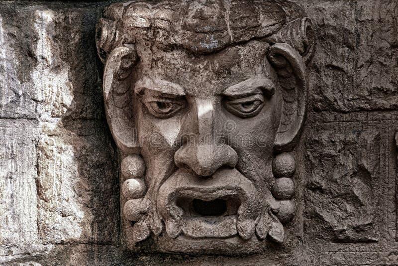 Bajorrelieve de piedra una clase de una cabeza de un demonio imagenes de archivo