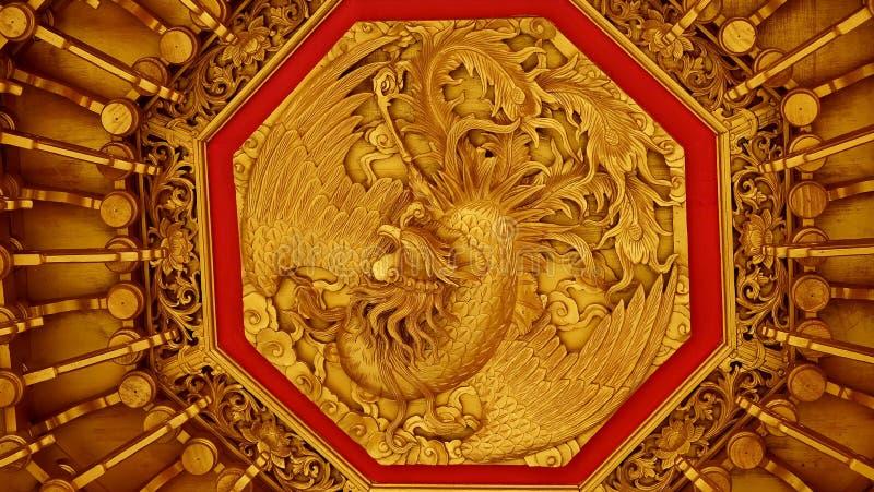 Bajorrelieve del oro del estilo chino del dragón, cisne en un templo chino imagenes de archivo