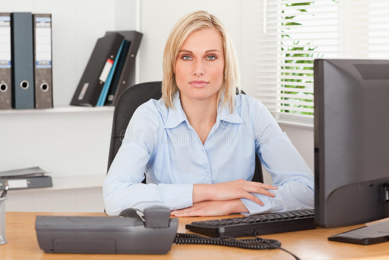 bak allvarlig sittande kvinna för skrivbord royaltyfria foton