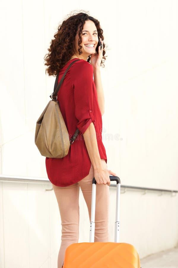 Bak av den unga kvinnan som går med resväskan och talar på mobiltelefonen royaltyfri fotografi