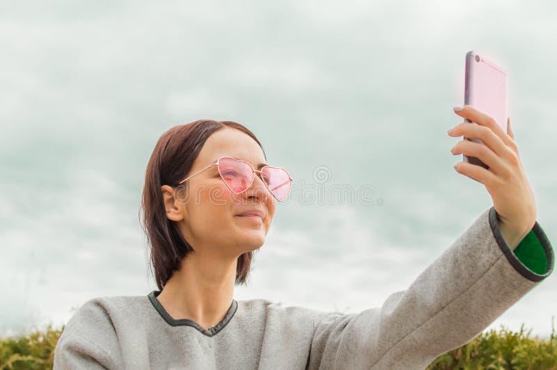 bak bokflickaexponeringsglas som döljer anteckningsbokståenden gör selfie på telefonen blå sky för bakgrund royaltyfri bild