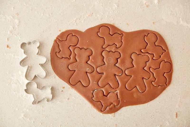 Bak de koekjes van de Kerstmispeperkoek, die in keuken koken royalty-vrije stock afbeeldingen