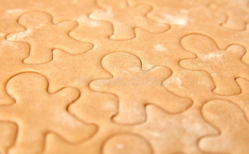 Bak de koekjes van de Kerstmispeperkoek, die in keuken koken stock foto