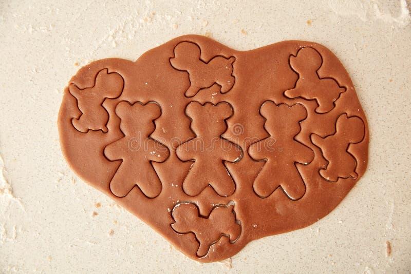 Bak de koekjes van de Kerstmispeperkoek, die in keuken koken stock afbeeldingen