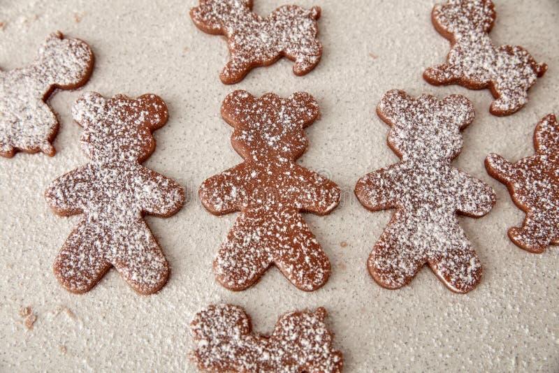 Bak de koekjes van de Kerstmispeperkoek, die in keuken koken stock fotografie