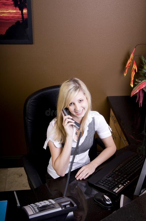bak fungerande barn för blond skrivbordkvinna arkivfoton