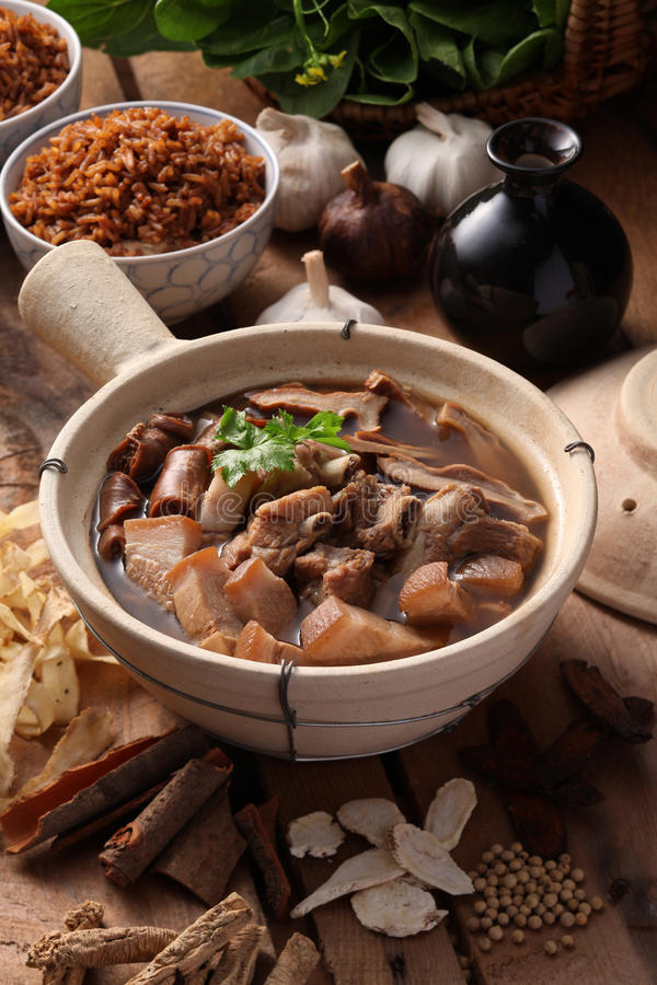 Bak kuh teh. A Malaysian herbal pork dish with herbs as background royalty free stock image