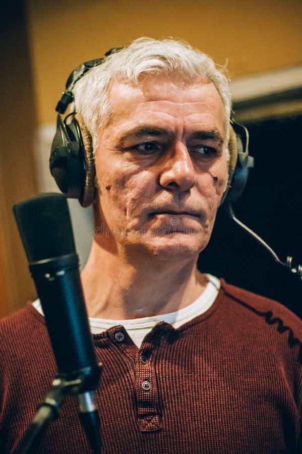 Bak plats Berömd alternativ manlig sångareövning som sjunger på mikrofonen arkivbild