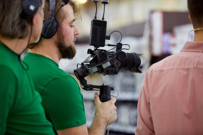 Bak platserna av filmskytte- eller videoproduktion och filmbes?ttningen team med kamerautrustning p? utomhus- l?ge royaltyfri bild