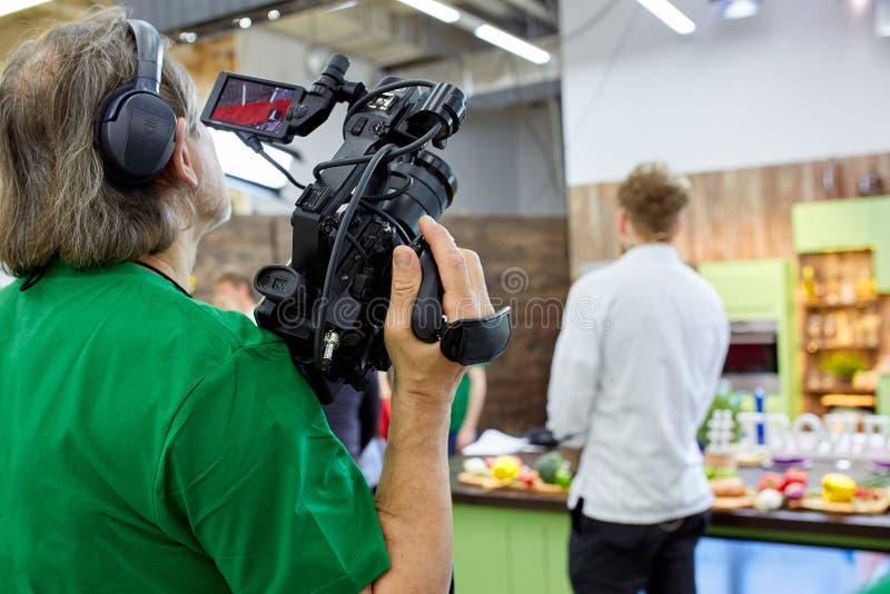 Bak platserna av filmskytte- eller videoproduktion och filmbes?ttningen team med kamerautrustning p? utomhus- l?ge arkivbild