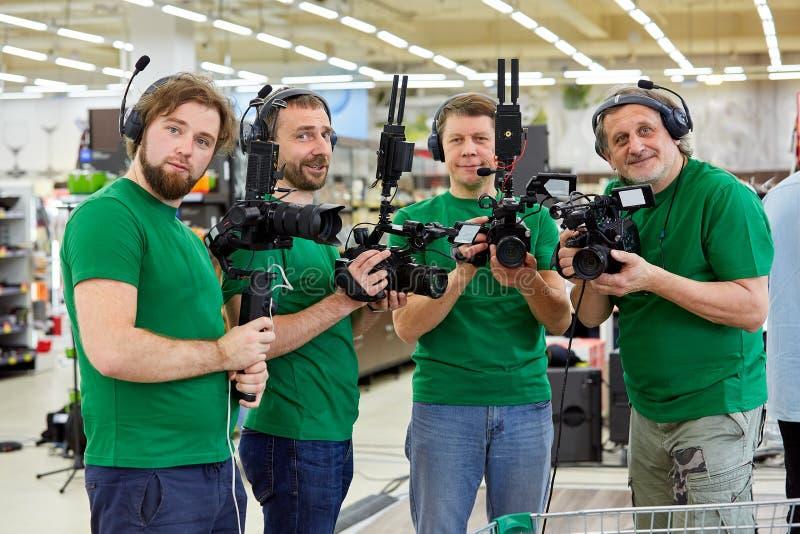 Bak platserna av filmskytte- eller videoproduktion och filmbes?ttningen team med kamerautrustning p? utomhus- l?ge arkivfoto