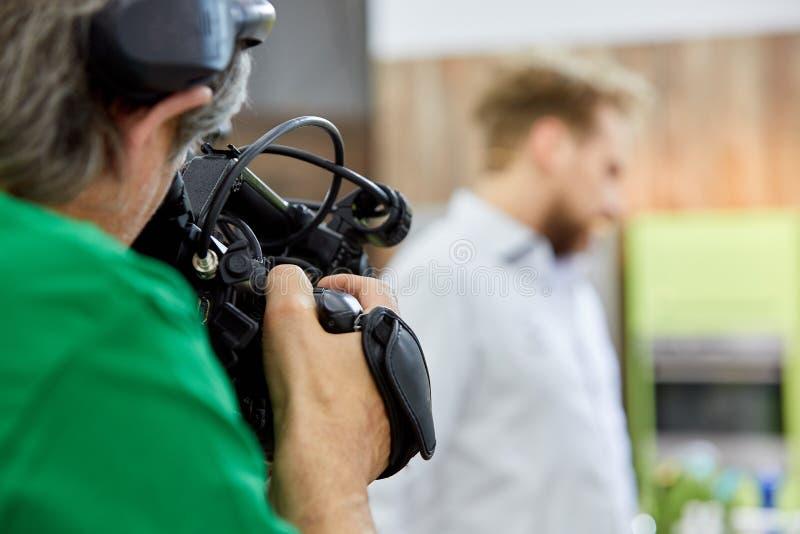 Bak platserna av filmskytte- eller videoproduktion och filmbes?ttningen team med kamerautrustning p? utomhus- l?ge royaltyfria bilder