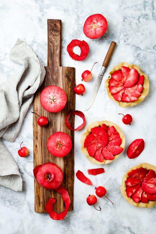 Baka äpplepajer över den vita marmortabellen, bästa sikt Laga mat mini- tarts med nya röda äpplen Baya Marisa royaltyfria bilder