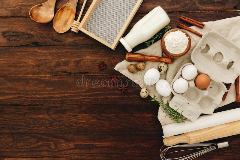 Baka eller receptingrediensägg, mjöl, mjölkar, breder smör på, sockrar på trätabellen royaltyfri fotografi