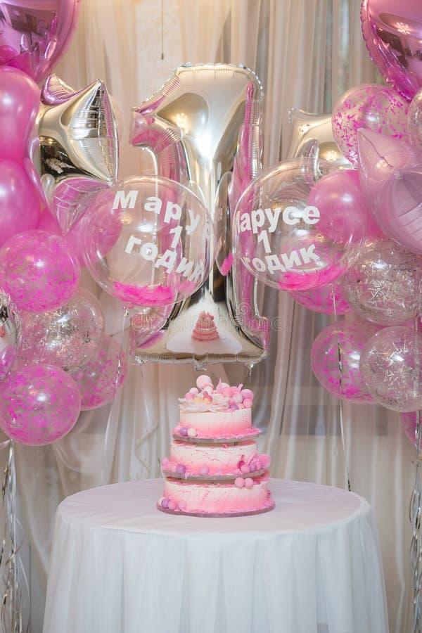 Baka ihop från flera rader för den första födelsedagen på en bakgrund av dekoren av ballonger med inskriften i ryss Marusya 1 år arkivfoto