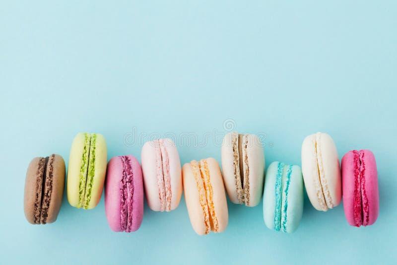 Baka ihop macaron eller makron på turkosbakgrund från över, färgrika mandelkakor, bästa sikt arkivbild