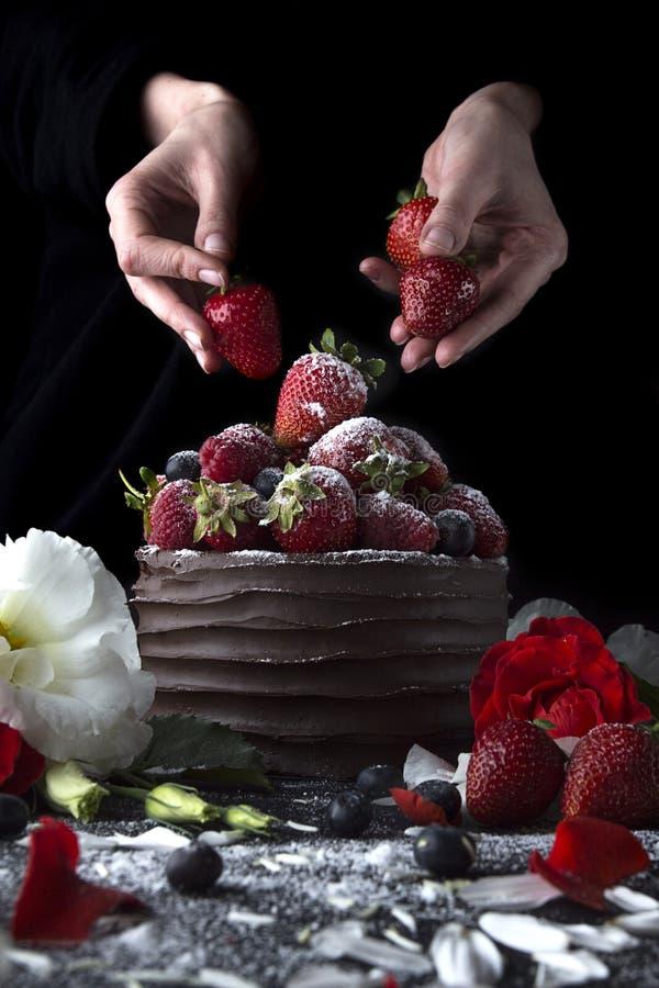 Baka ihop med choklad som dekorerar med jordgubben och blommor royaltyfri fotografi